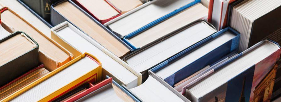Książki losowo ułożone na półce